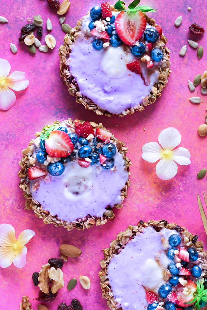 Nut and Seed Fruit Yogurt Tarts [Vegan] - These tarts not only look super pretty, they are filled with vegan blueberry yogurt and surrounded by an array of delicious mixed nuts like walnuts, almonds, sunflower seeds and peanuts. Add some fresh berries on top and enjoy this sweet treat as breakfast, snack or dessert. NeuroticMommy.com #healthy #vegan #easter #tarts