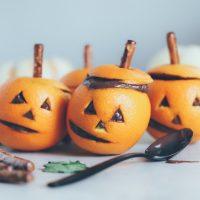 Vegan Chocolate Pudding Orange Jack O' Lanterns - Oranges filled with vegan chocolate pudding making this a fun healthy snack option for Halloween! NeuroticMommy.com #vegan #halloween #healthysnacks