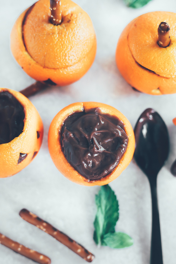 Vegan Chocolate Pudding Orange Jack O' Lanterns - Oranges filled with vegan chocolate pudding making this a fun healthy snack option for Halloween! NeuroticMommy.com #vegan #halloween #healthysnacks
