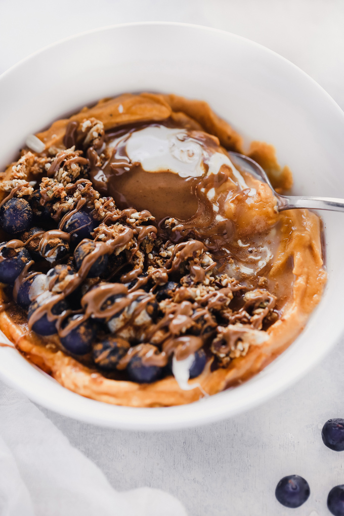 Vegan Sweet Potato Breakfast Bowl - Topped with blueberries, almond butter, and dairy free yogurt, this is packed with fiber, healthy fats and so easy to make! You can meal prep this and have it ready to go with all the right ingredients to fuel your day! NeuroticMommy.com #vegan #breakfast #sweetpotatoes