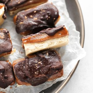 Homemade Vegan Twix Bars - A traditional shortbread crust layered with gooey caramel filling and a sweet dark chocolate topping. A delicious vegan remake to a classic recipe. NeuroticMommy.com #vegantwix