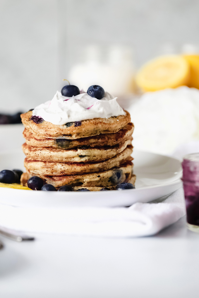 Vegan Blueberry Lemon Buttermilk Pancakes - The BEST VEGAN Fluffy Buttermilk Pancakes you'll ever try! With blueberries and lemon in every bite and topped with coconut whip cream, maple syrup and a blueberry compote. NeuroticMommy.com #vegan #pancakes