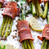 Vegan Bacon Wrapped Asparagus - Super easy and delicious low carb, vegan keto friendly side dish to make anytime. Crispy bacon wrapped around asparagus topped with vegan parmesan and a sprinkle of lemon is all sorts of perfect. NeuroticMommy.com #vegan #thanksgiving #veganketo #keto